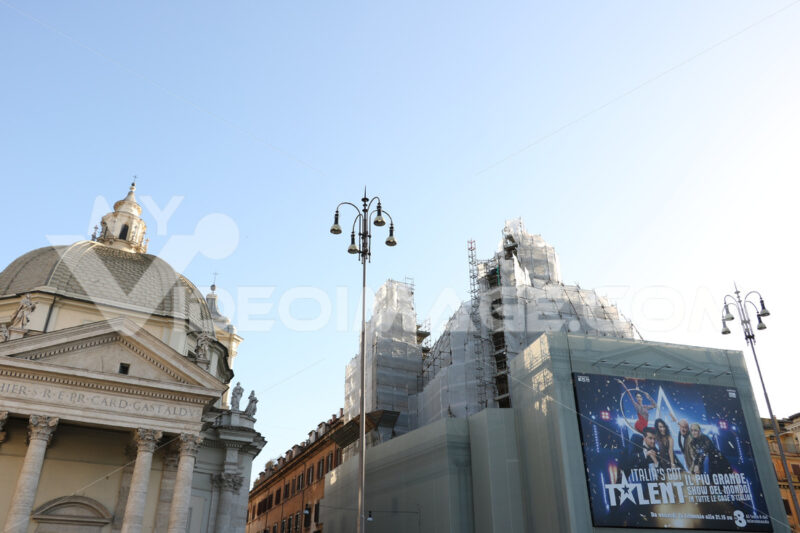Two twin churches in Piazza del Popolo in Rome. Building site for the restoration of a church with scaffolding and advertising sheets. - LEphotoart.com