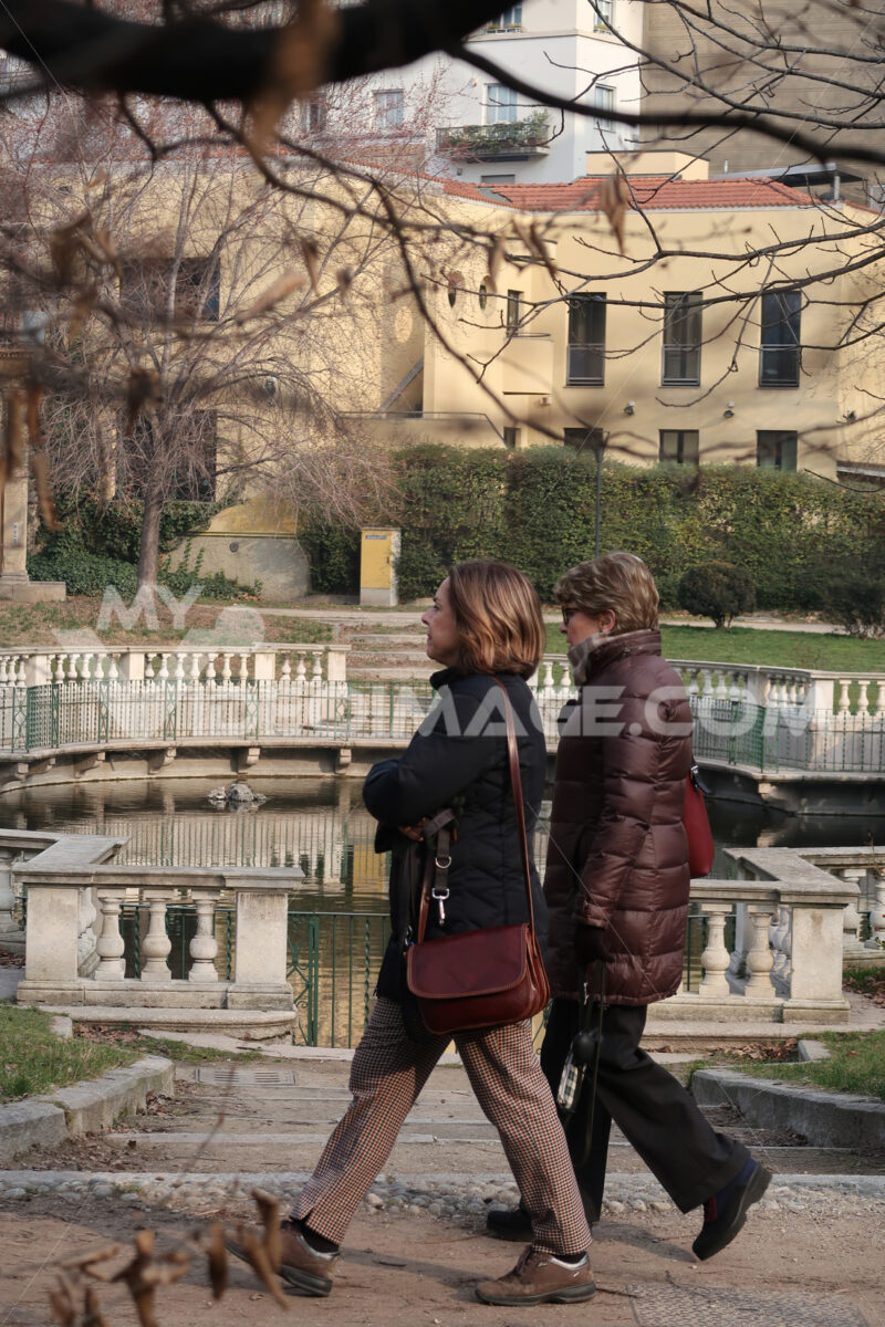 Two women stroll in the Guastalla gardens in Milan. Water tank in the Guastalla gardens. Traditional Italian garden with a pond in the city center. - MyVideoimage.com