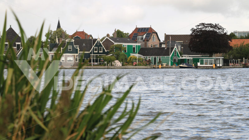 Typical Dutch houses. Typical Dutch houses on the canal near Amsterdam. In the land of windmills there are many traditional houses along the river. - MyVideoimage.com | Foto stock & Video footage