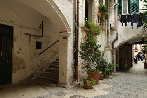 Typical Mediterranean house in an alleyway in the city of Bari. Facade painted white and climbing green plants. Foto Bari photo.