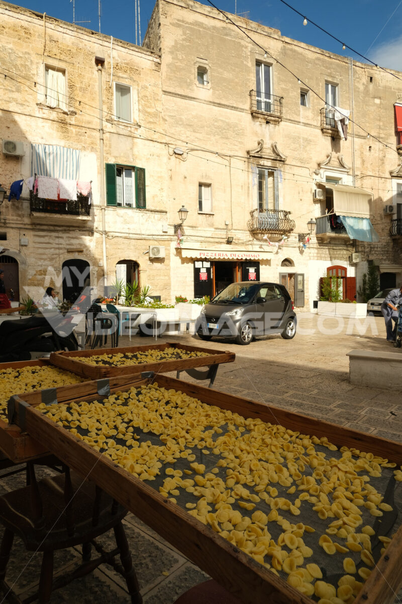 Typical Mediterranean pasta Orecchiette made to dry. Ancient houses in the alleys of the city of Bari. - MyVideoimage.com