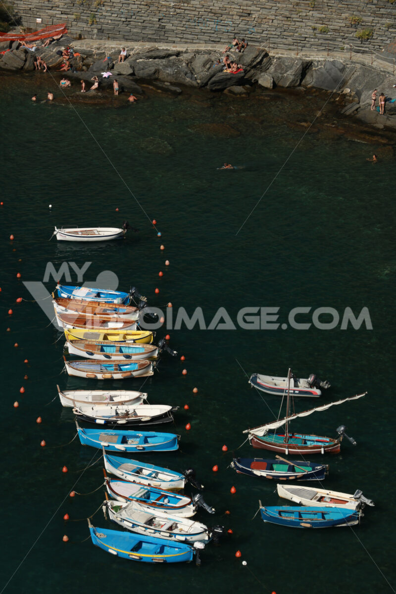 Typical colored fishing boats, Gozzo type, anchored in the harbor of Vernazza in the Cinque Terre. Top view of the path. - MyVideoimage.com