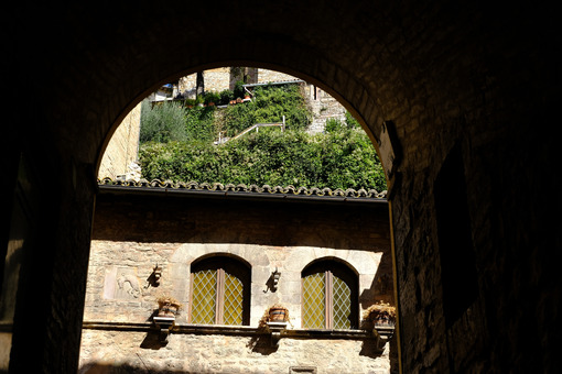Typical windows in the facade of an ancient Italian house in Assisi. Decorate with flower vases. - MyVideoimage.com