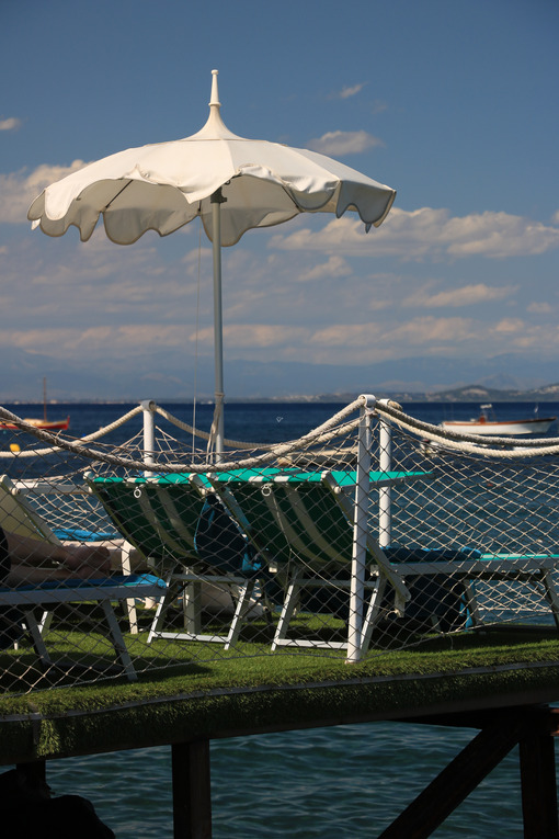 Umbrella on a pier with a white parapet on the sea of Ischia. In - MyVideoimage.com