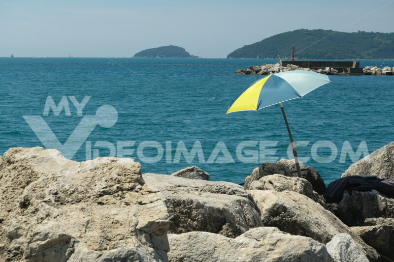 Umbrella on the cliff an boats. Colorful beach umbrella on the cliff. Stock photos. - MyVideoimage.com   Foto stock & Video footage