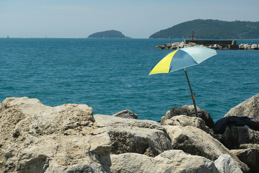 Umbrella on the cliff an boats. Colorful beach umbrella on the cliff. Stock photos. - MyVideoimage.com | Foto stock & Video footage