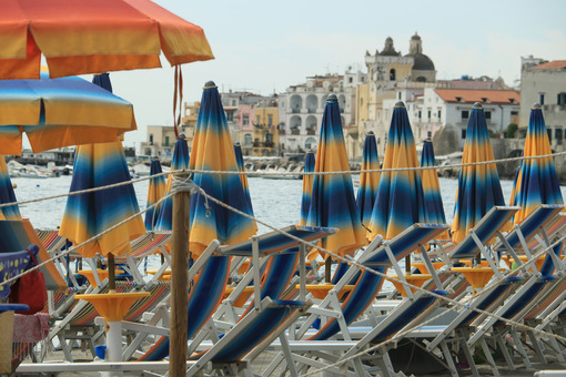 Umbrellas and deckchairs on the beach of Ischia Porto. Foto Ischia photos.