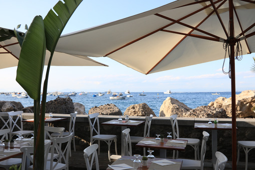 Umbrellas of a romantic seaside restaurant. In the background th - MyVideoimage.com