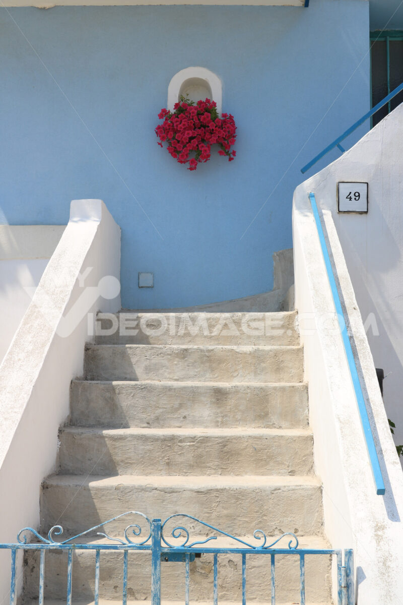 Vase of red flowers. Vase of red flowers on Mediterranean house facade. Staircase wit - MyVideoimage.com | Foto stock & Video footage