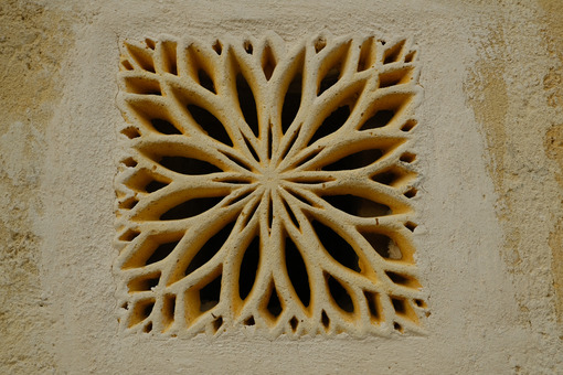 Ventilation grid on the front of a house. Made of stone with a decorative shape. Matera, Italy. - MyVideoimage.com