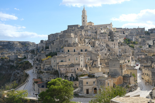 View of the city of Matera in Italy. Church with bell tower and houses built in beige tuff stone. - MyVideoimage.com