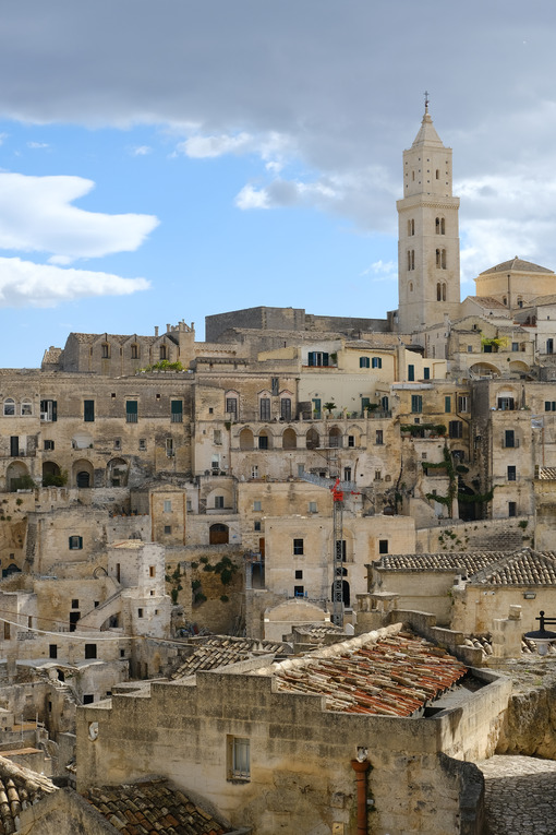 View of the city of Matera in Italy. Church with bell tower and houses built in beige tuff stone. - LEphotoart.com