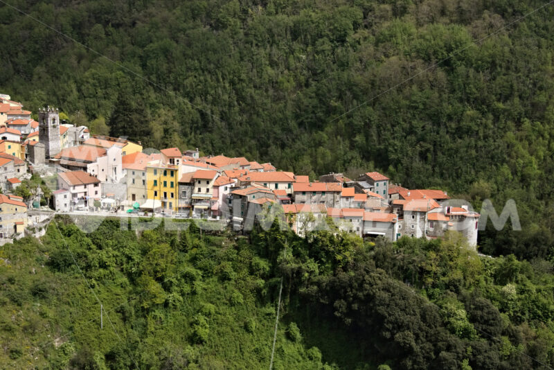 View of the town of Colonnata, famous for the production of lard. The walls of the houses in stone and white Carrara marble. Woods background. Northern Tuscany. Colonnata, Carrara, Italy. - MyVideoimage.com