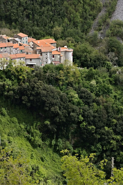 View of the town of Colonnata, famous for the production of lard. The walls of the houses in stone and white Carrara marble. Woods background. Northern Tuscany. Colonnata, Carrara, Italy. - LEphotoart.com