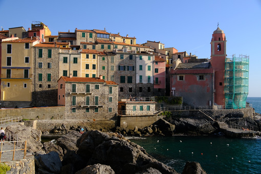 Village of Tellaro di Lerici near the Cinque Terre. View of the village illuminated by the light of the sunset. Houses, church and bell tower. - MyVideoimage.com