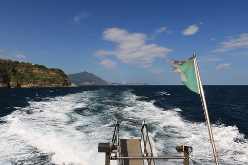 Wake of water left by a ship in the blue sea. In the background the island of Ischia (Naples) with the port and the lighthouse. - MyVideoimage.com