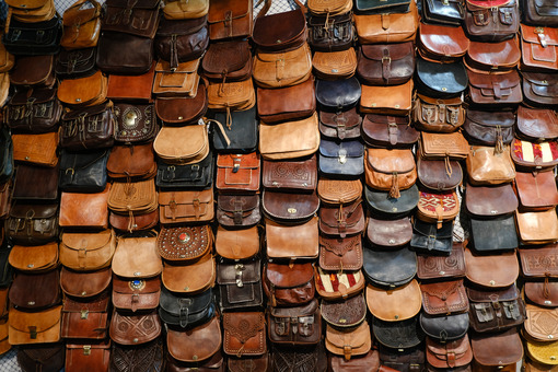 Wall display of leather bags at the craft fair. Leather bags in various colors, from brown to black. - MyVideoimage.com