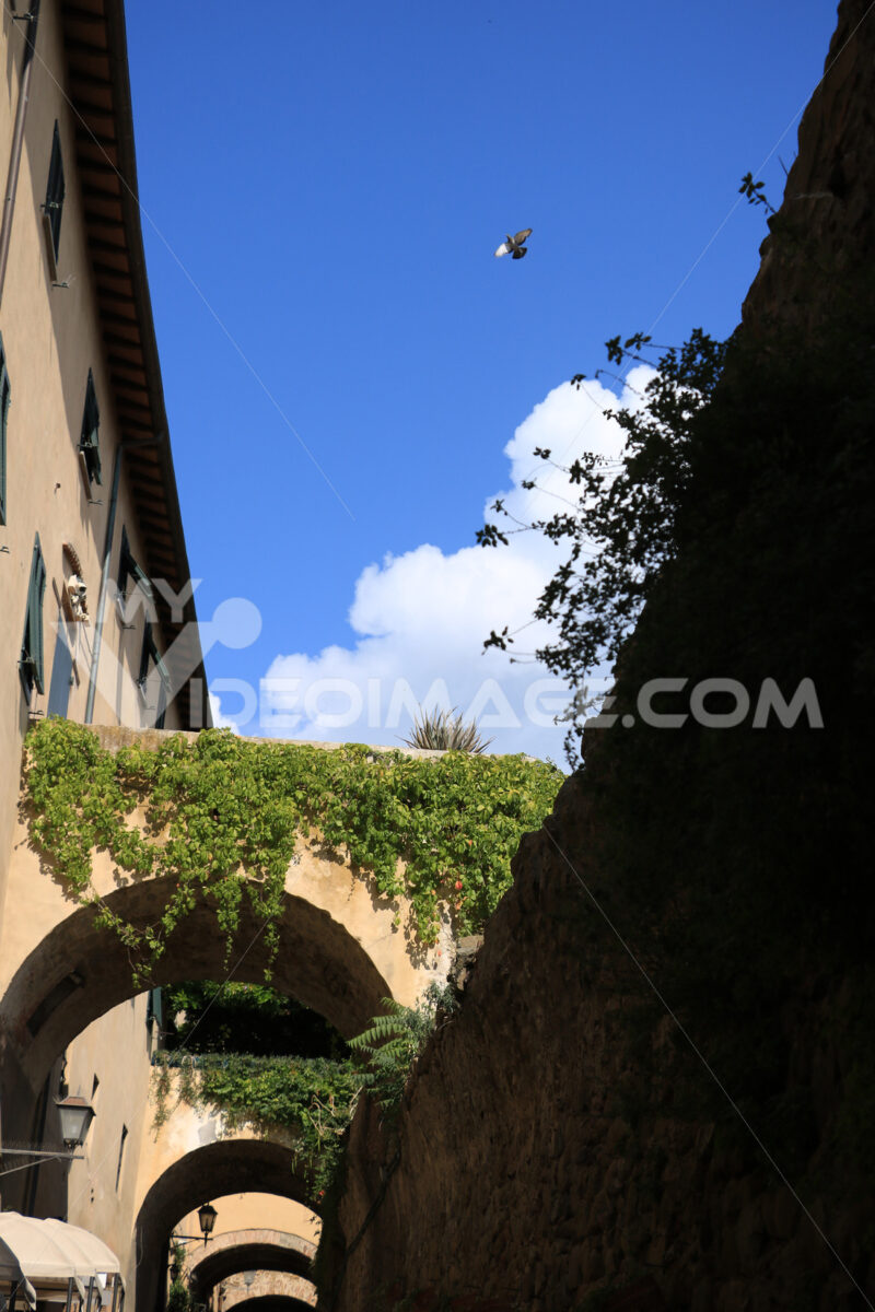 Walls with arches connected to the houses of Castiglione della Pescaia. An ancient village in the Tuscan Maremma built on a hill facing the sea. - MyVideoimage.com