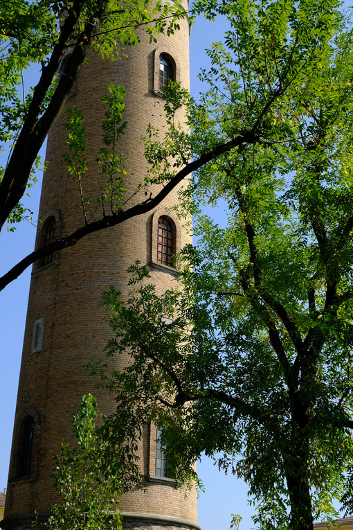 Water tower. Cylindrical brick tower soars into the blue sky. Stock photos. - MyVideoimage.com | Foto stock & Video footage
