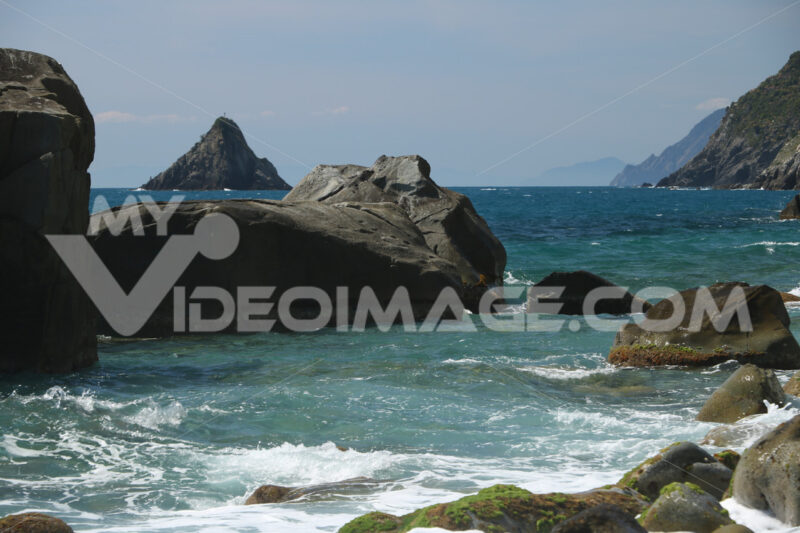 Waves of the sea break on the beach and on the rocks near the Cinque Terre. The waves break on the wild and natural beach with sheer mountains. - MyVideoimage.com