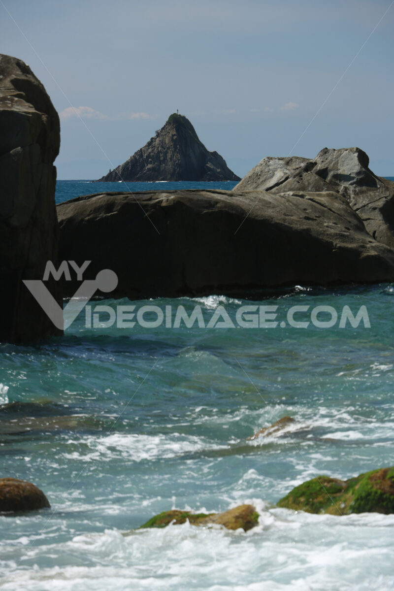 Waves of the sea break on the beach and on the rocks near the Cinque Terre. The waves break on the wild and natural beach with sheer mountains. - LEphotoart.com