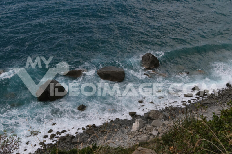 Waves of the sea break on the beach and on the rocks near the Cinque Terre. Uncontaminated wild and natural environment in the Ligurian sea. - MyVideoimage.com