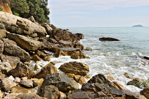 Waves of the sea break on the rocks. Mountain rocks of yellow color. and light-colored sea. - MyVideoimage.com