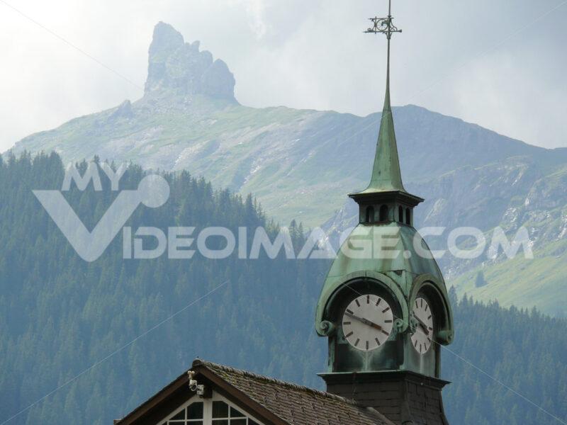 Wengen, Switzerland. Mountain and church with clock. - MyVideoimage.com