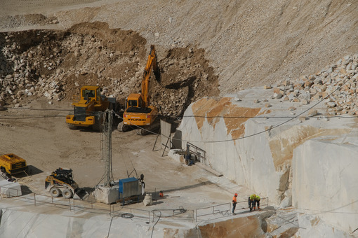 White Carrara marble quarry. A mechanical shovel and a backhoe with a pneumatic hammer break and move large stones. - LEphotoart.com