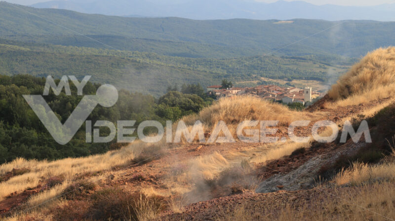 White rocks at the Biancane geothermal park. Steam jets and the town of Monterotondo Marittimo, near Larderello in Tuscany. - MyVideoimage.com