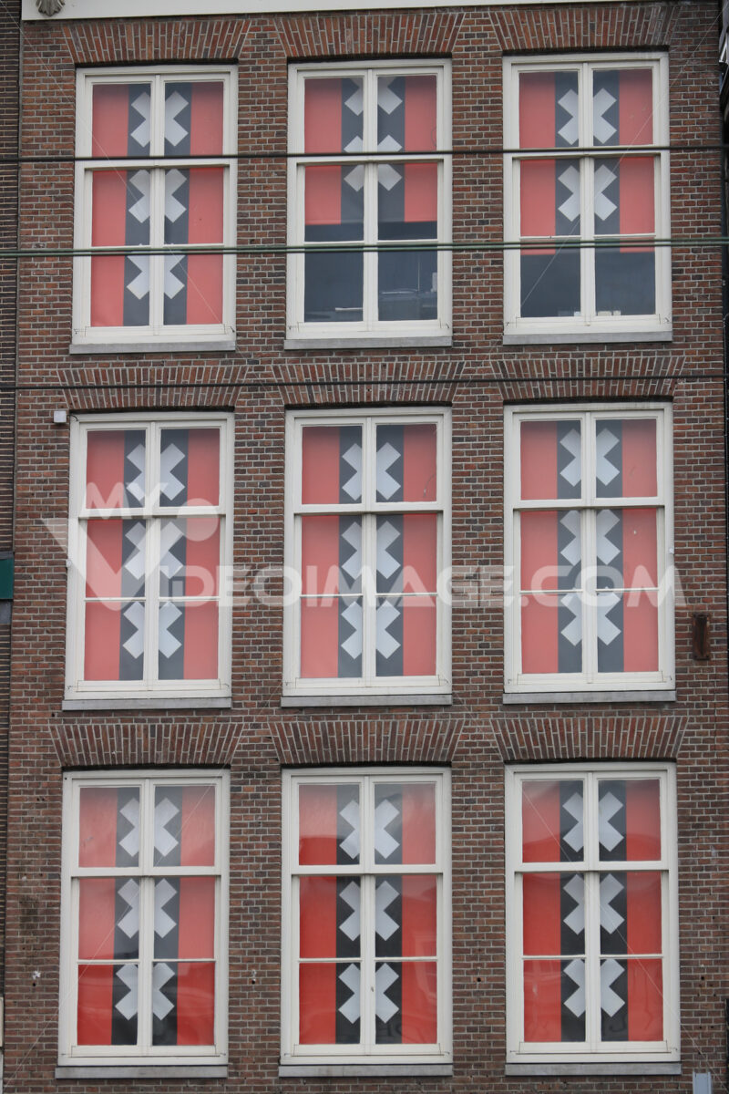 Windows with curtains in the colors of the Amsterdam flag. Red and black flag with the Saint Andrew crosses. - MyVideoimage.com