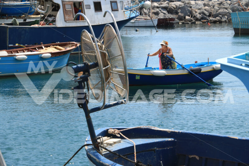Woman on rowboat. Woman with rowing boat in the port of Corricella. - MyVideoimage.com | Foto stock & Video footage
