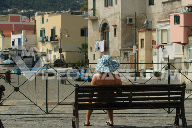 Woman with hat sitting on a bench. In the background old houses - MyVideoimage.com
