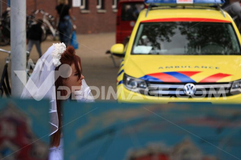 Woman with wedding dress sitting near yellow ambulance. - MyVideoimage.com