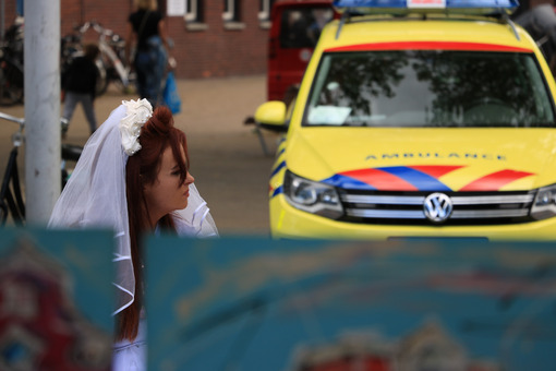 Woman with wedding dress sitting near yellow ambulance. - MyVideoimage.com