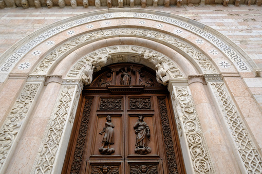 Wooden door and portal in light marble carved of the Cathedral of San Feliciano in Foligno. - LEphotoart.com