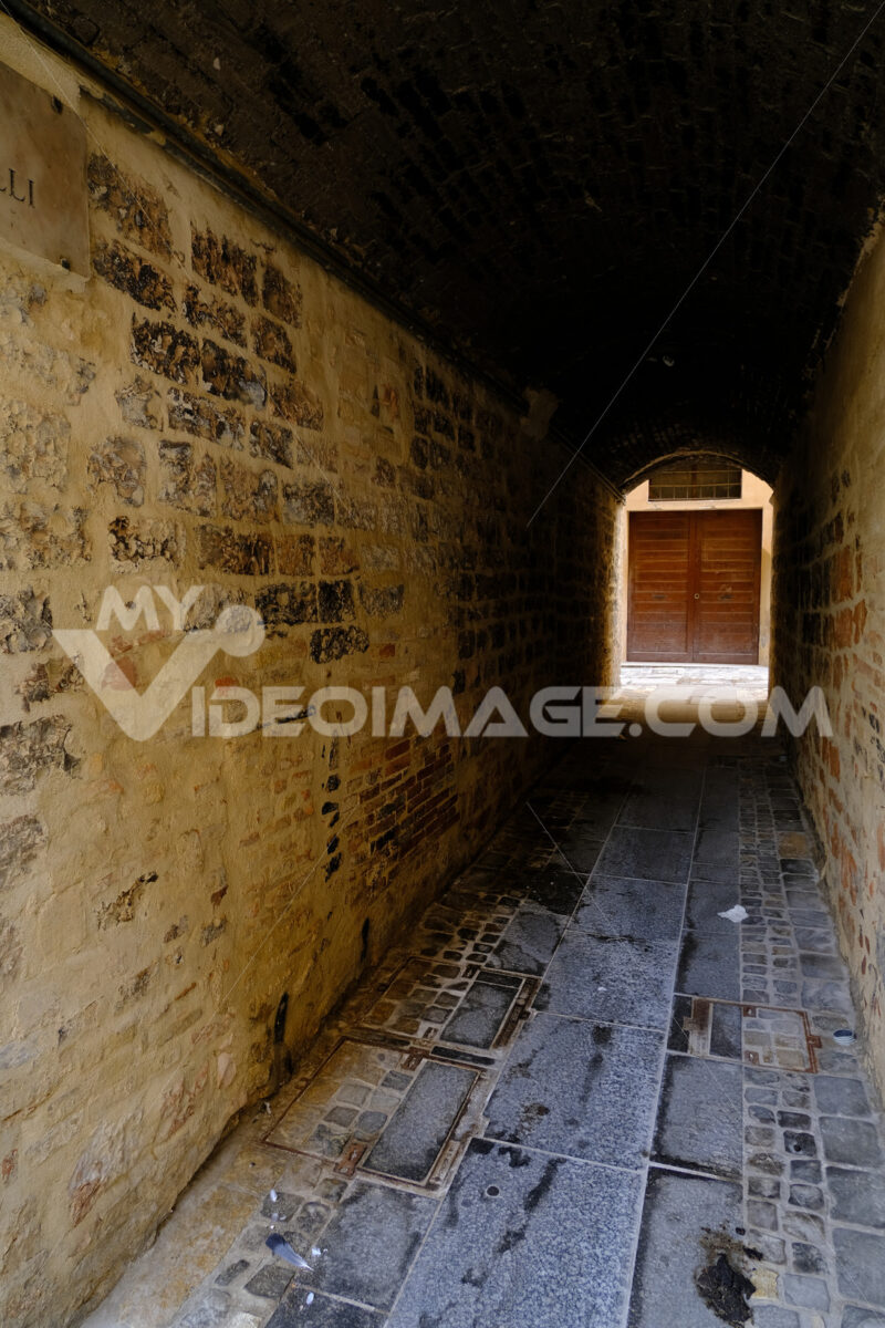 Wooden door at the end of a covered street, closed and dark. - MyVideoimage.com | Foto stock & Video footage