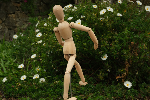 Wooden mannequin in the midst of spring flowers. Mediterranean garden with cistus with white rose flowers and rotating model. - MyVideoimage.com