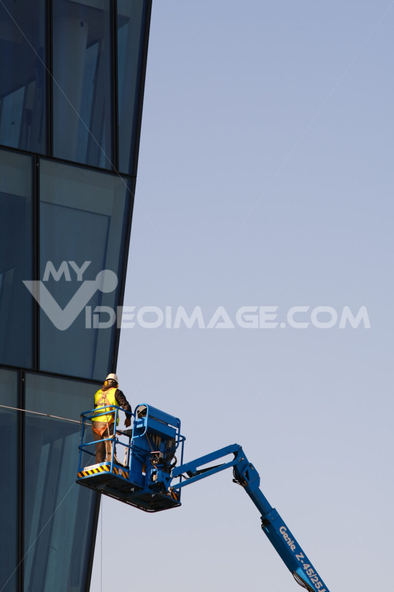 Worker on an elevator basket cleans the facade of a glass-clad building. - MyVideoimage.com