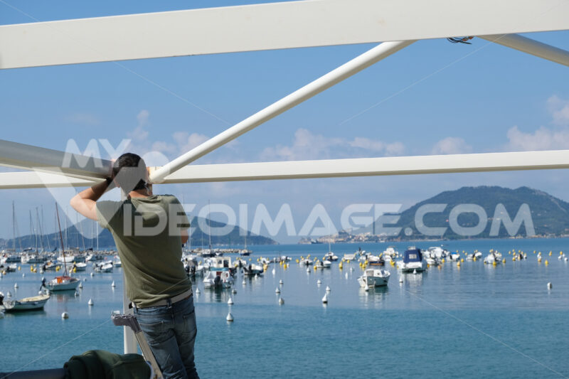 Worker performs maintenance work on a seaside gazebo. Blue sky and sea background with boats. - MyVideoimage.com | Foto stock & Video footage