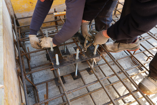 Workers mount steel plates with anchor bolts for columns on a reinforced concrete foundation. - LEphotoart.com