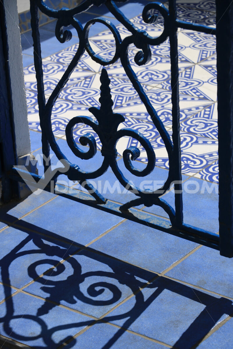 Wrought iron gate. Blue and white ceramic tiles. - MyVideoimage.com